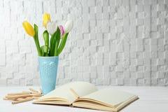Vase mit Tulpen und Notizbuch Lizenzfreies Stockbild