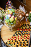 Vase with multicolored macaroon cookies with fresh forest berries, popcorn at the festive table in a restaurant. Candy bar at a party in the French style. Table Stock Images