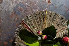 Vase from newspapers with camellia  plant on a rusty table. Royalty Free Stock Images