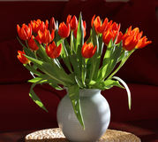 Vase of Orange Tulips in Modern Interior. Vase with Orange Tulips in Modern Interior. Crackle-glazed vase, round place-mat of water hyacinth; background of Stock Photos