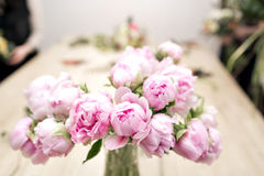 Vase of peonies in the foreground. soft focus. Workshop florist, making bouquets and flower arrangements. Woman Stock Photo