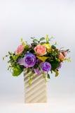 Vase. Plastic flower on a  ceramic vase with white background Royalty Free Stock Photography