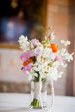Vase of pretty flowers sitting on a table Royalty Free Stock Photography