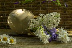 A vase with purple and white flowers on a rustic wooden. Background stock images