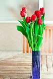 Vase of red flowers on garden table Royalty Free Stock Image