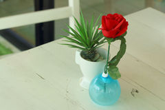 Vase of red flowers on a table Royalty Free Stock Photo