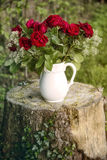 Vase with red roses on tree stump Stock Images