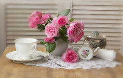 Vase of roses and cup of tea  Royalty Free Stock Photo