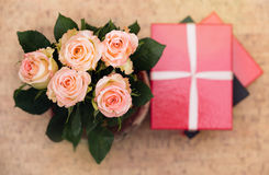 Vase with roses and gift with ribbon.  Stock Image