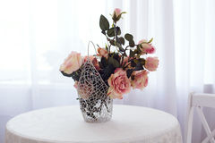 Vase with roses. Is standing on the table in front of window Stock Photography
