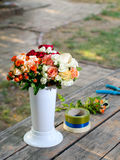 Vase with roses, tapes and scissors on wooden table Royalty Free Stock Images
