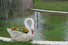 Vase in the shape of swans on the shore of a pond Stock Photography