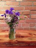 Vase of summer wildflowers on wooden table against brick wall Stock Photography