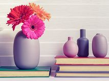 A vase with three gerberas is on an old book. Nearby are three books one on another. royalty free stock photo
