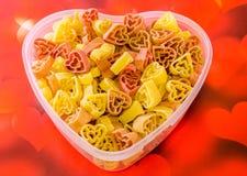 Vase transparent à forme de coeur (cuvette) rempli (le rouge, jaunissent une orange) de pâtes colorées de forme de coeur, fond co Image libre de droits