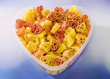 Vase transparent à forme de coeur (cuvette) rempli (le rouge, jaunissent une orange) de pâtes colorées de forme de coeur, fond co Photos libres de droits