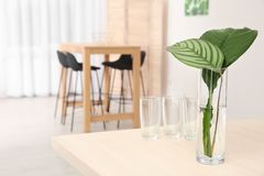 Vase with tropical leaves on table indoors. Interior design element Stock Images