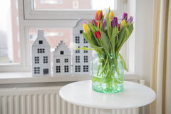 Vase with tulips in interior Royalty Free Stock Photos