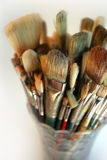 Vase of used brushes. A very shallow depth-of-field image of used paintbrushes stacked in a glass vase. Focus is on the front brushes. (large image - 10 x 15 stock photography