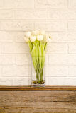 Vase of white flowers on a wooden hearth. White flowers in a vase sitting against white brick Stock Image
