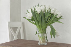 Vase with white tulips on a table Stock Images