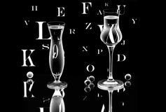 A vase and a wineglass on the mirror. A vase and a wineglass with Latin letters and small glass balls on the mirror Stock Photo