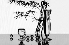 A vase, a wineglass and some little glass balls. On the mirror stock image