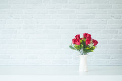 Vase on a wooden table. With a white brick wall Royalty Free Stock Photo