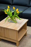 Vase with yellow tulips on modern wooden coffee table. Vase with yellow spring tulips on modern wooden coffee table royalty free stock photo