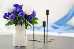 Vasen av blått blommar i modern vardagsrum fotografering för bildbyråer
