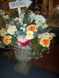 Vasen med fejkar plast- blommor Royaltyfri Foto