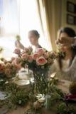 Vasen med rosa färger arbeta i trädgården rosor på blommamasterclassbakgrund Arkivfoto
