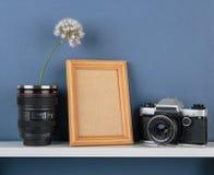 Vasen mit Blume und alter Kamera auf weißem Regal auf blauem wallpap Stockbild