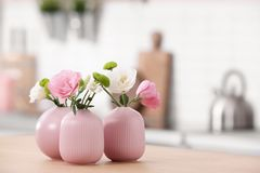 Vases with beautiful flowers on table in kitchen interior. Space for text stock photos