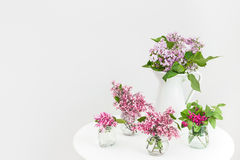 Vases with blooming spring flowers on a round table Royalty Free Stock Photography