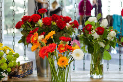 Vases with different flowers. In the windowof florist's shop Stock Photos