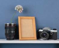 Vases with flower and old camera on white  shelf on blue wallpap Stock Image