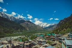 Vashishtdorp op bergen de achtergrond van Himalayan en blauwe hemel met wolken Stock Afbeelding
