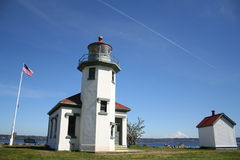 Vashon Island Lighthouse, Washington, USA. Point Robinson Lighthouse on Vashon Island with contrail in the blue sky and Mt Rainier in distance Royalty Free Stock Photo