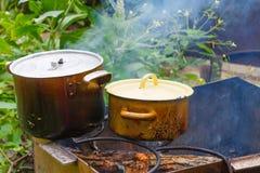 Vasi anneriti sul fuoco, cucinante all'aperto Immagini Stock Libere da Diritti