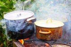 Vasi anneriti sul fuoco, cucinante all'aperto Fotografia Stock Libera da Diritti