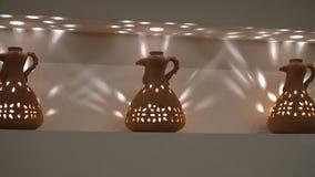 Vasi dell'argilla sotto forma di galli sullo scaffale La candela sta bruciando dentro interno e comodità domestici archivi video