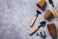 Vasi della torba ed altri strumenti di giardino sulla tavola con lo spazio della copia fotografia stock libera da diritti