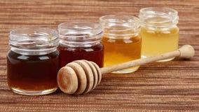 Vasi in pieno del drizzler di legno del miele Fotografia Stock