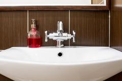 Vask med den skinande vattenkranen och tvål Arkivbild