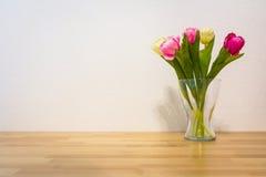 Vaso branco do vidro da parede da tabela de madeira amarela cor-de-rosa das tulipas foto de stock royalty free