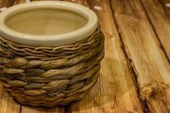 Vaso ceramico beige di vimini d'annata su fondo di legno Immagine Stock
