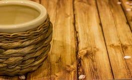 Vaso ceramico beige di vimini d'annata su fondo di legno Fotografia Stock