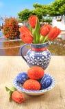 Vaso ceramico blu con i tulipani e le uova di Pasqua all'aperto Immagini Stock