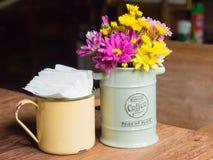 Vaso com ferro e flores, estilo do vintage na tabela Imagem de Stock